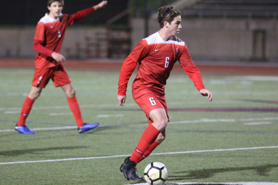 Coppell junior Sebastian Blaas makes eye contact with his teammates as he gets ready to pass the ball during the game on Feb. 8 against Flower Mound. The Cowboys won 2-1 against the Jaguars.