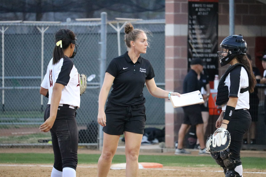 Coppell Assistant Coach Mackenzie Reeves visits with Coppell senior Nora Rodriguez and sophomore Dafne Mercado during third inning Coppell ISD Baseball/Softball Complex on Friday. The Cowgirls lost to Jaguars, 3-2.