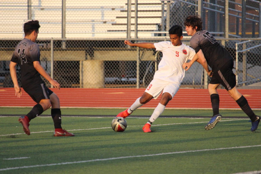 Coppell junior forward Tom Vazhekatt passes the ball upfield during the match against Denton Guyer on Friday at Falcon Stadium at Lake Dallas. After a scoreless regulation and two overtime periods, Coppell won,  0-0 (4-3), in the Class 6A Region I bi-district match.