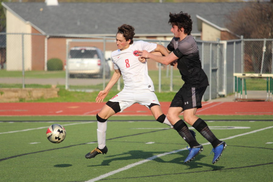 Coppell senior forward Joe Ruedi fights for possession  on Friday at Falcon Stadium at Lake Dallas. After a scoreless regulation and two overtime periods, Coppell won,  0-0 (4-3), in the Class 6A Region I bi-district match.