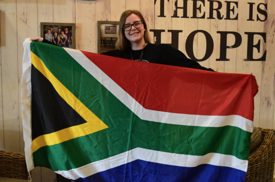 CHS9+freshman+Caitlin+Stringer+holds+up+the+South+African+flag+at+American+Tea+and+Coffee+to+represent+her+South+African+heritage.+Stringer+moved+to+Coppell+from+South+Africa+before+the+school+year+started+because+her+family+wanted+to+find+better+economic+opportunities.+Photo+taken+by+Mari+Pletta.%0A