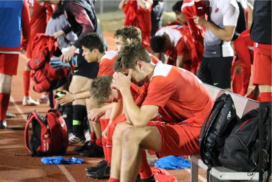 Coppell senior midfielder Jeremy Basso and his teammates react after their match against Grand Prairie at Mustang-Panther Stadium on Tuesday. The Cowboys lost, 3-1, in second round of bi-district playoffs.