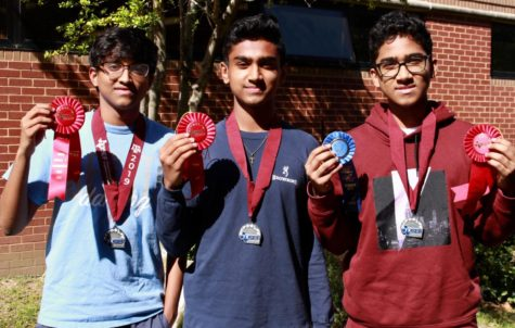 Coppell High School sophomore Karthik Karupiah, junior Tom Vazhekatt and sophomore Zach Vazhekatt showcase their awards from the annual Texas Science and Engineering Fair in the CHS garden on April 8. These three students finished second place in the TXSEF state science fair in the Plants Science division.