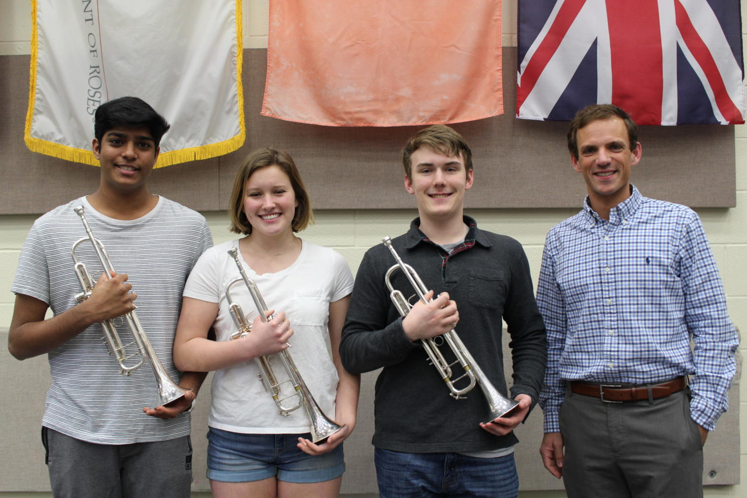 Coppell High School senior Supratik Pochampally, junior Terri Rauschenbach and senior Trevor Holmes stand with CISD Trumpet Instructor Dr. Jared Hunt in the CHS band room. The Ensemble won first place in the Trumpet Ensemble Division at the National Trumpet Competition on March 16 at the University of Kentucky in Lexington, Ky.
