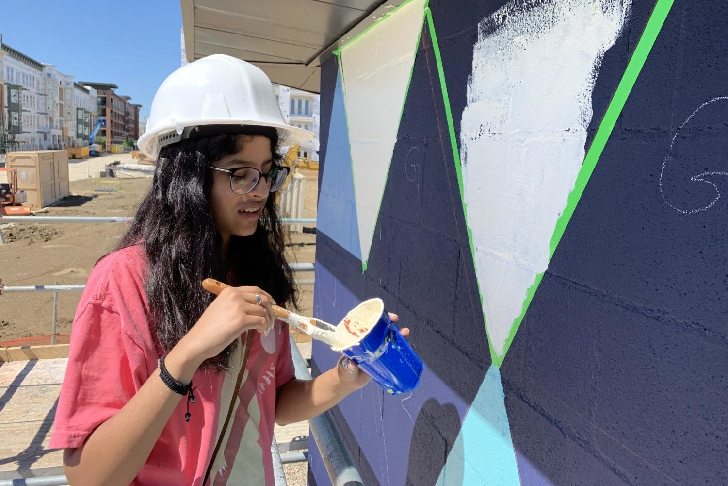 Coppell High School sophomore Ishita Sisodia helps paint a mural at Pump Station in Cypress Waters yesterday. CHS art teacher David Bearden provided students the opportunity to create a mural at Cypress Waters.