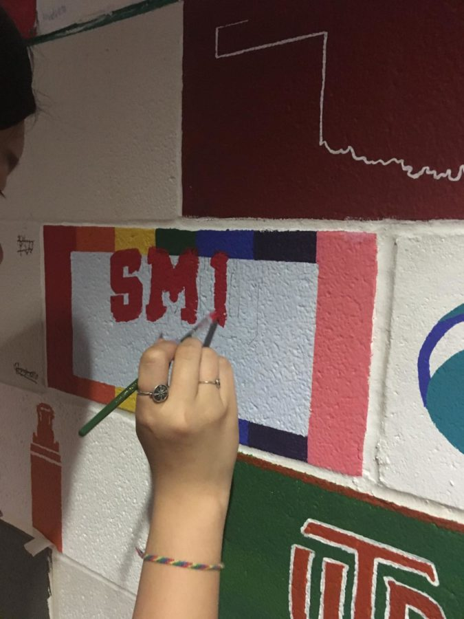 New Tech High @ Coppell senior Joie Lew paints her senior brick with the Southern Methodist University logo in New Tech main hallway on May 8. Every April, seniors at New Tech have the opportunity to paint a brick.
