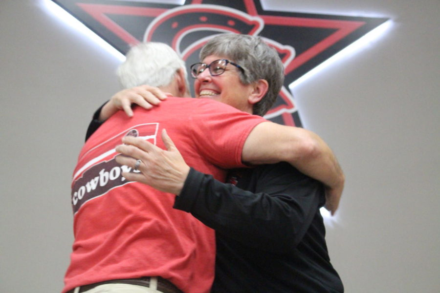 Former Coppell Middle School East principal Laura Springer hugs Coppell High School outdoor adventures teacher Bill Parker on the cafeteria stage on May 9. Springer is the newly announced 2019-20 CHS principal.