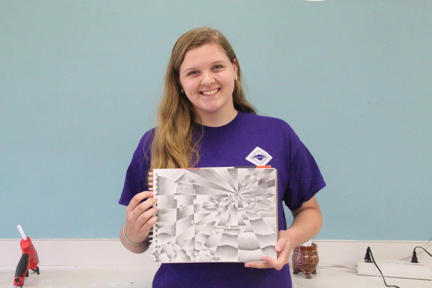 Coppell High School sophomore Jordan Buffington shows of her sketch for David Bearden's Art 1 honors class. Buffington is painting a mural with professional artist Mary Lacy in Cypress Waters on Sunday.