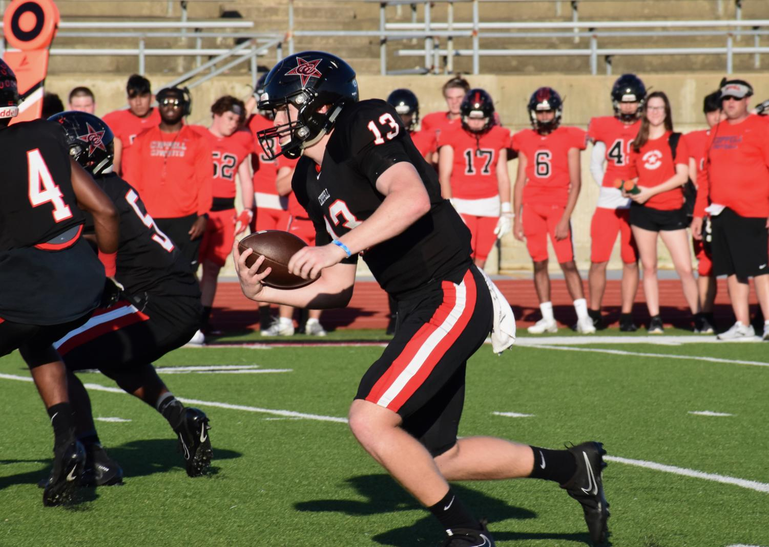 The Black team junior quarterback Drew Cerniglia rushing towards a first down during the annual spring football game. The Black team came up on top 14-7 during the friendly game.