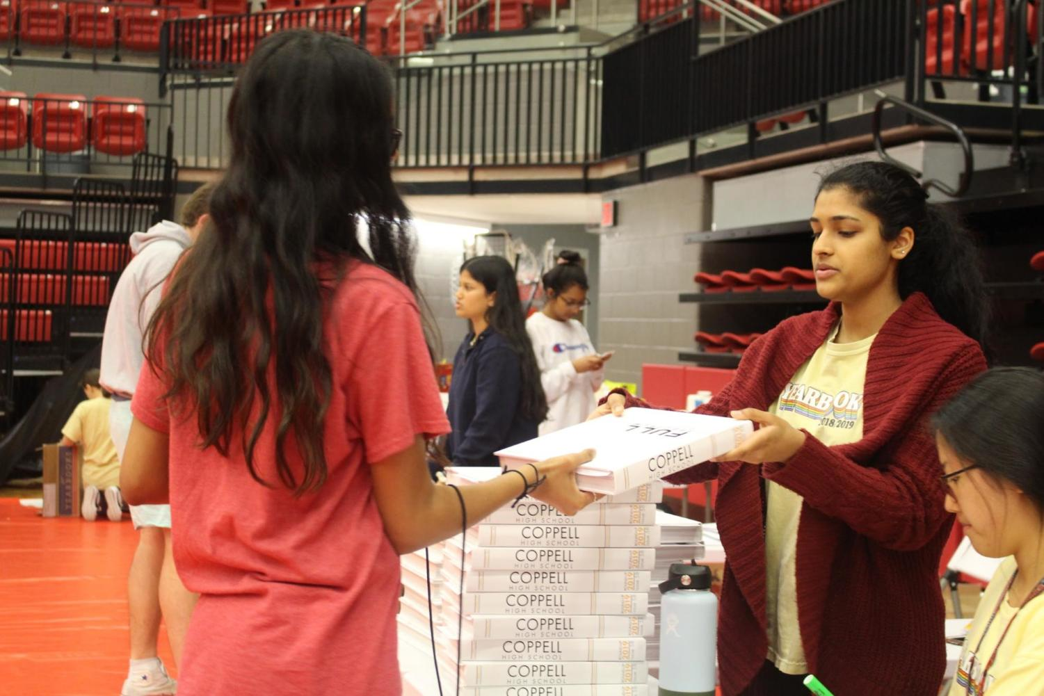 Coppell High School junior Anais Hartley receives her Round-Up yearbook today during sixth period. The yearbook pick up will be held at the Arena all throughout the day at Coppell High School for CHS students. Photo by Laura Amador-Toro
