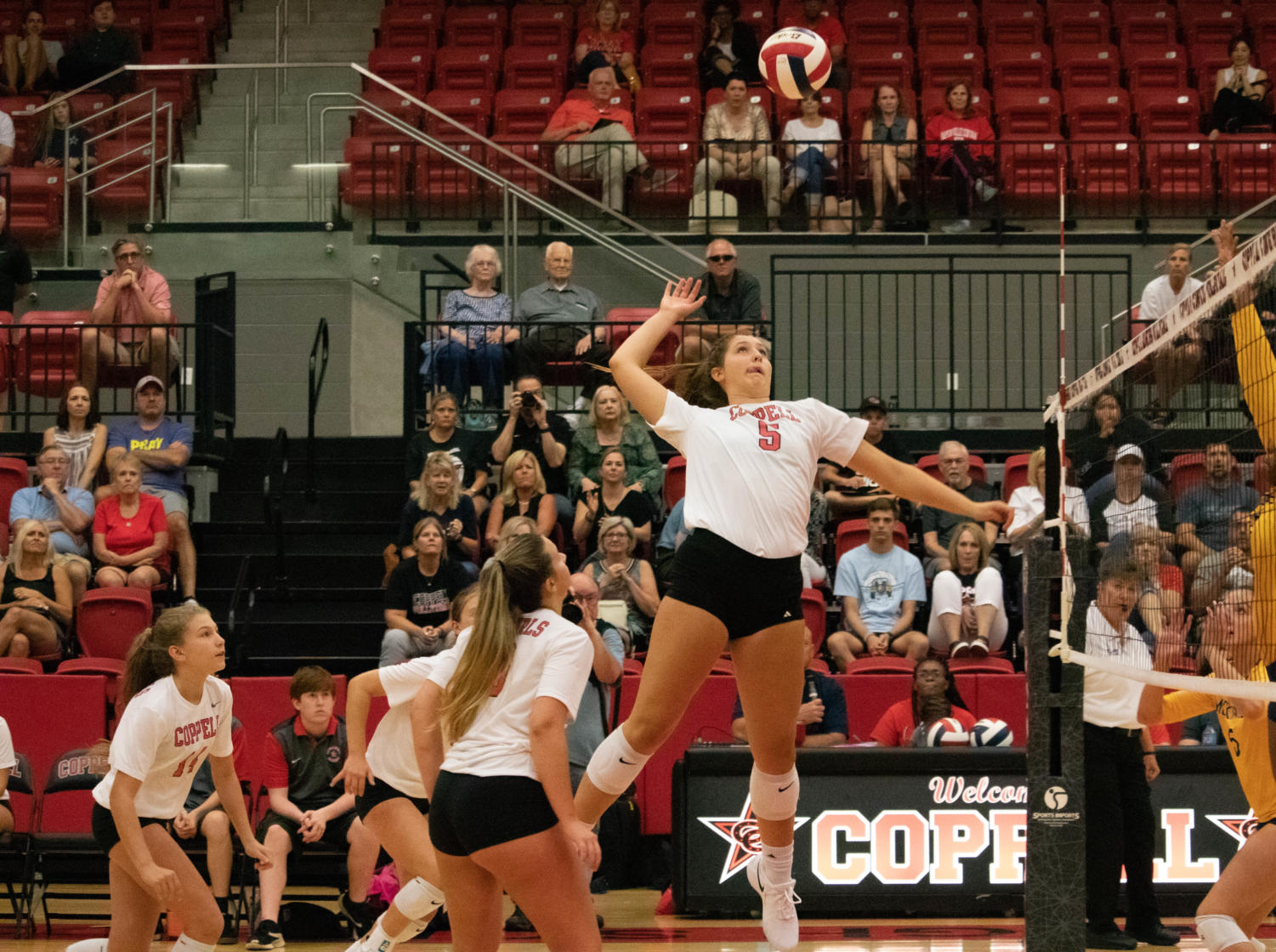 Coppell junior middle blocker Madison Gilliland goes for a spike during Tuesday's volleyball match against McKinney at the CHS Arena. After three close sets, the Cowgirls defeated the Lionettes, 3-0.