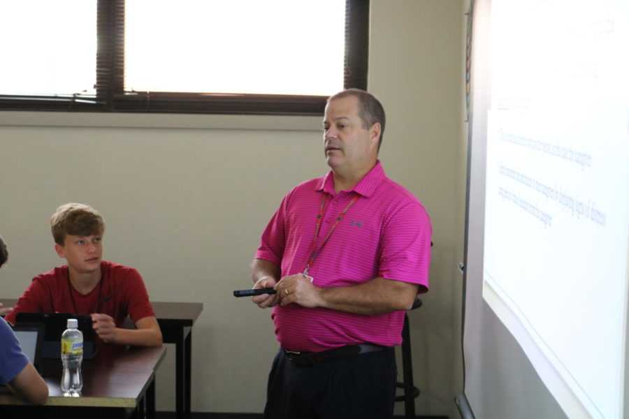 Coppell High School psychology and economics teacher Eric Walker wears a pink shirt while teaching his class. Pink shirts are worn by teachers every Wednesday to raise awareness for breast cancer.