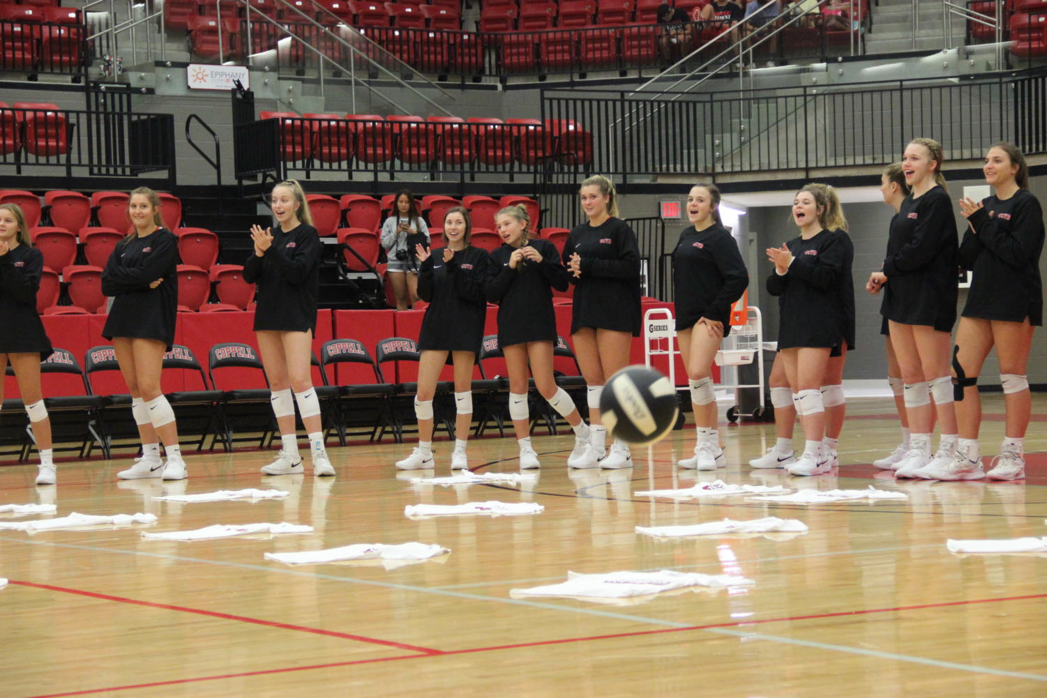 Coppell+varsity+volleyball+players+celebrate+after+an+elementary+school+student+successfully+serves+during+Elementary+Night.+The+Coppell+volleyball+team+hosted+Elementary+Night+on+Tuesday+in+the+CHS+Arena+before+the+varsity+match+against+Arlington+Martin.