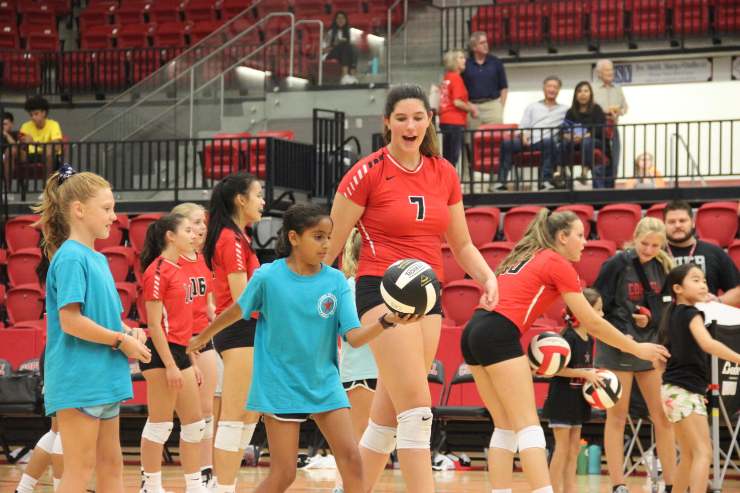 Coppell+JV+sophomore+middle+blocker+Aley+Clent+helps+elementary+school+students+serve+to+win+T-shirts.+The+Coppell+volleyball+team+hosted+Elementary+Night+on+Tuesday+in+the+CHS+Arena+before+the+varsity+match+against+Arlington+Martin.