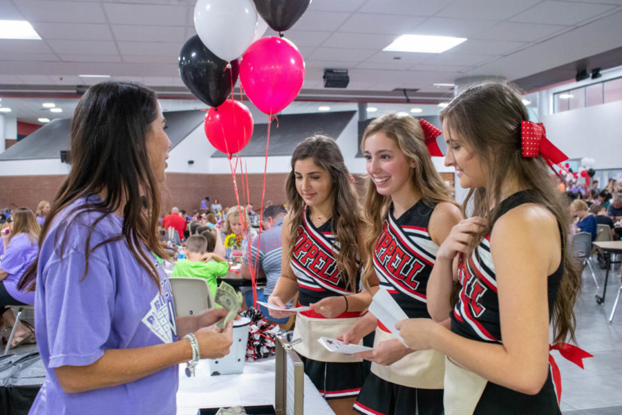 Coppell High School juniors Makaylie Montague, Kate Baird and Zoey Darkoch hand in their remaining Cheer Clinic Flyers to Nikki Darkoch (left) during the Cheer Bingo fundraiser on Friday. Cheer Bingo was held in the commons and is the CHS cheerleading team's biggest annual fundraiser.