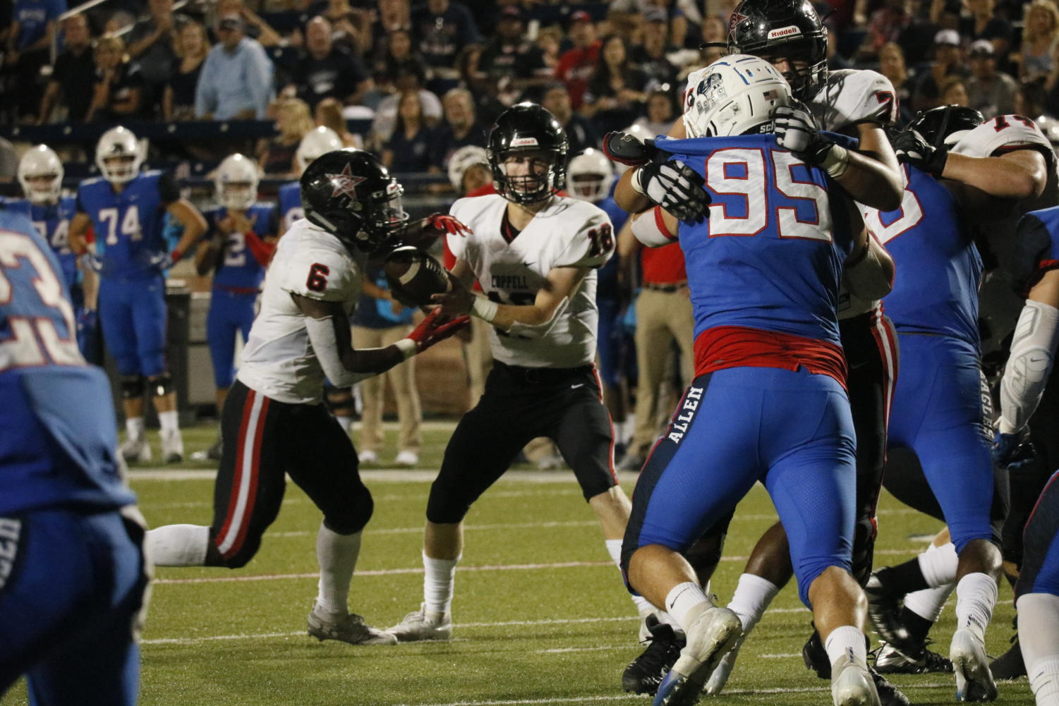 Coppell junior quarterback Ryan Walker hands off to junior running back Jason Ngwu as they near the endzone at Eagle Stadium on Friday night. The Cowboys kept up with Allen but eventually fell, 28-21, to the nationally-ranked team.