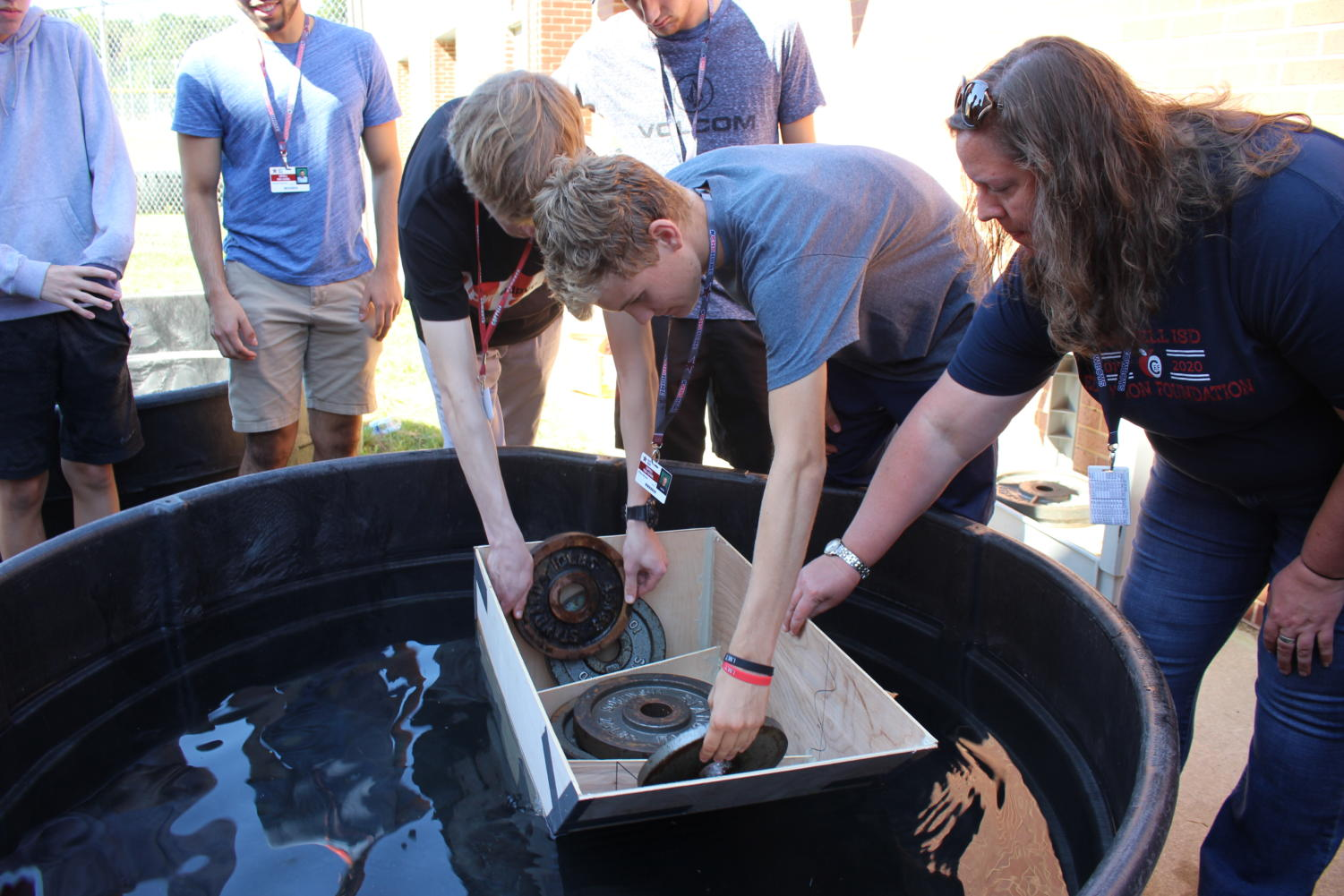 Coppell High School seniors Riley Warner and Josh Zawislak and CHS physics teacher Stephanie Sloane place weights into the students' boat, named The Acorn, at the back of the fieldhouse during sixth period. CHS AP Physics II classes created their own boats, which must hold a minimum of 10 pounds.