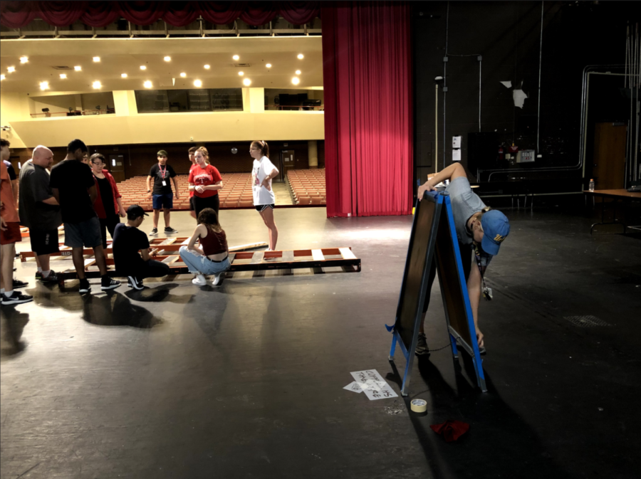 Coppell+High+School+theater+department+head+Karen+Ruth+cleans+a+sign+for+%E2%80%9CNewsies%E2%80%9D+on+the+CHS+Auditorium+stage+while+theater+students+finalize+props.+The+show+runs+from+Nov.+1-3%2C+9+and+10+in+the+CHS+Auditorium.