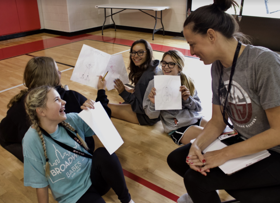 CHS9 Silver Stars coach and physical education teacher Hillary Clark listens to freshmen Lizzie Borchgardt, Annabelle Peterman, Mariana Delgadillo and Lucy Marz talk about what they drew from the lesson over communication skills during a team building activity in the main gym at CHS9 during eight period. Clark is the new Silver Stars coach and P.E teacher at CHS9. Photo taken by Neveah Jones.