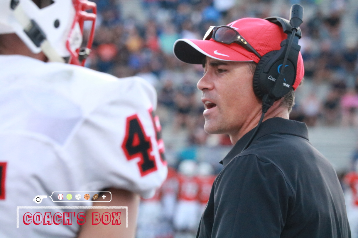 Coppell football defensive coordinator Justin Merchant discusses with the defense during the Cowboys season opener against the Sachse Mustangs last Friday. With more than 15 years of experience, Merchant hopes to improve the defense while preparing his athletes for the future.