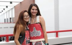 Coppell High School seniors Heather Lee and Caroline McConnell get their picture taken on the senior bridge on Friday. Senior girls wore overalls today for the first home football game of the year.