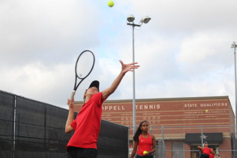 Coppell sophomore Cason Cole serves as the tennis team prepares to play Tyler Lee on Sept. 28, as sophomore Nandini Thalliparedy looks on at the CHS Tennis Center. The Coppell tennis team defeated Tyler Lee, 17-2.