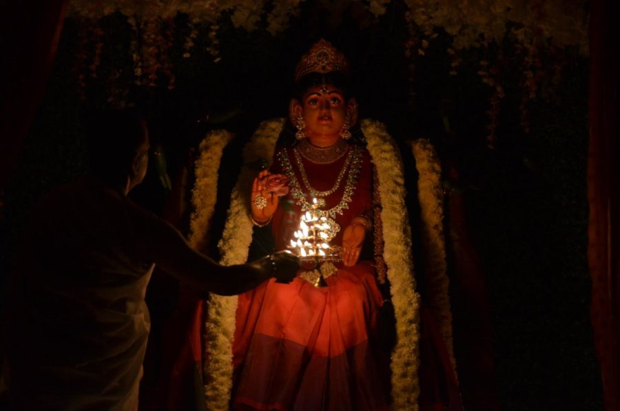 A+priest+turns+the+aarti%2C+a+plate+of+lamps+rotated+clockwise%2C+in+front+of+deities+as+an+expression+of+gratitude+and+prayer+in+front+of+Bala+Tripura+Sundari+Devi.+Navaratri+is+an+annual+Hindu+festival+that+celebrates+femininity+and+life+through+worshipping+different+incarnations+of+the+mother+goddess%2C+or+Devi.+Photo+courtesy+Sri+Hari+Hara+Peetham