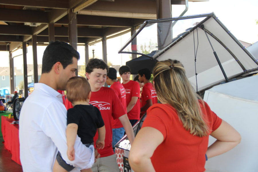 Coppell+High+School+junior+Solar+Car+Team+vice+president+Marcos+Morales+describes+how+solar+car+works+to+car+enthusiasts+Sargon+and+Rachel+Daniel+on+Sunday+at+the+Coppell+Old+Town+Pavilion.+Proceeds+from+the+Coppell+Car+Show+go+towards+the+CHS+Solar+Car+Team.
