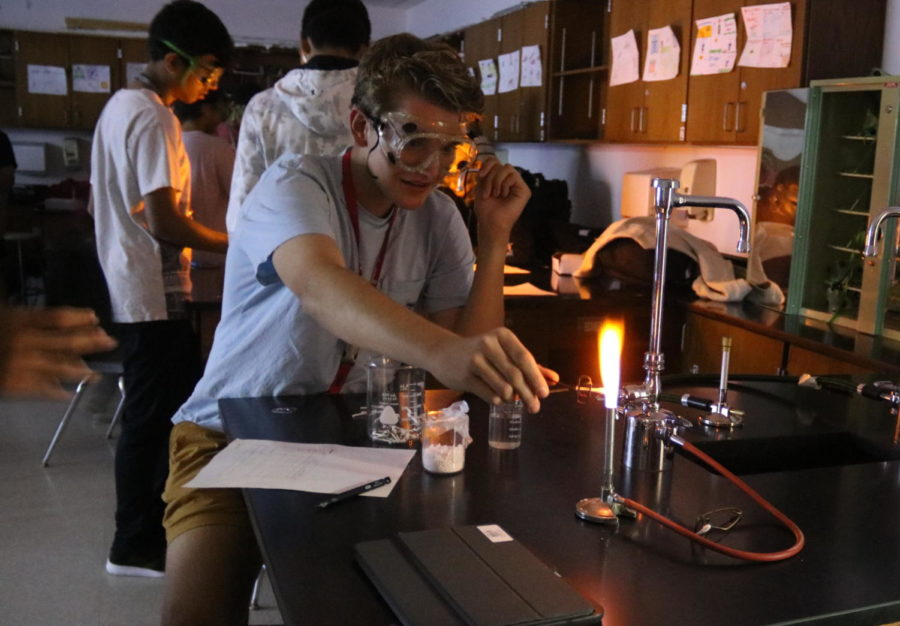 Coppell High School sophomore Sven Collins observes the color change in the flames from the Bunsen burner in Mashal Khan's third period chemistry class in C102 on Wednesday. Chemistry is currently in their electromagnetic spectrum unit.