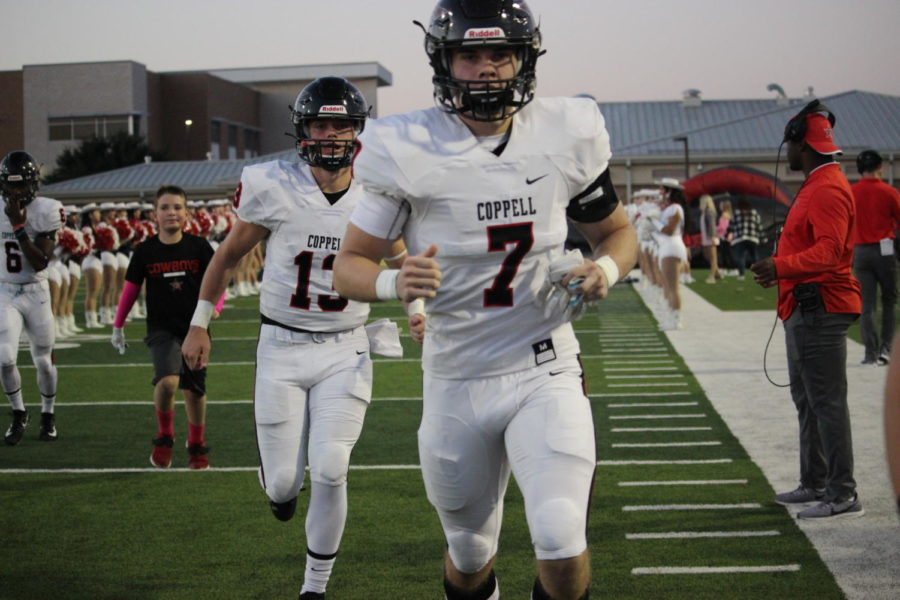 Coppell+sophomore+quarterback+Landry+Fee+and+senior+defensive+back+Gavin+Osteen+run+out+during+the+game+against+Marcus+on+Oct.+18+at+Marauders+Stadium.+The+Cowboys+face+Irving+tonight+at+7+p.m.+at+Buddy+Echols+Field+for+the+Homecoming+game.