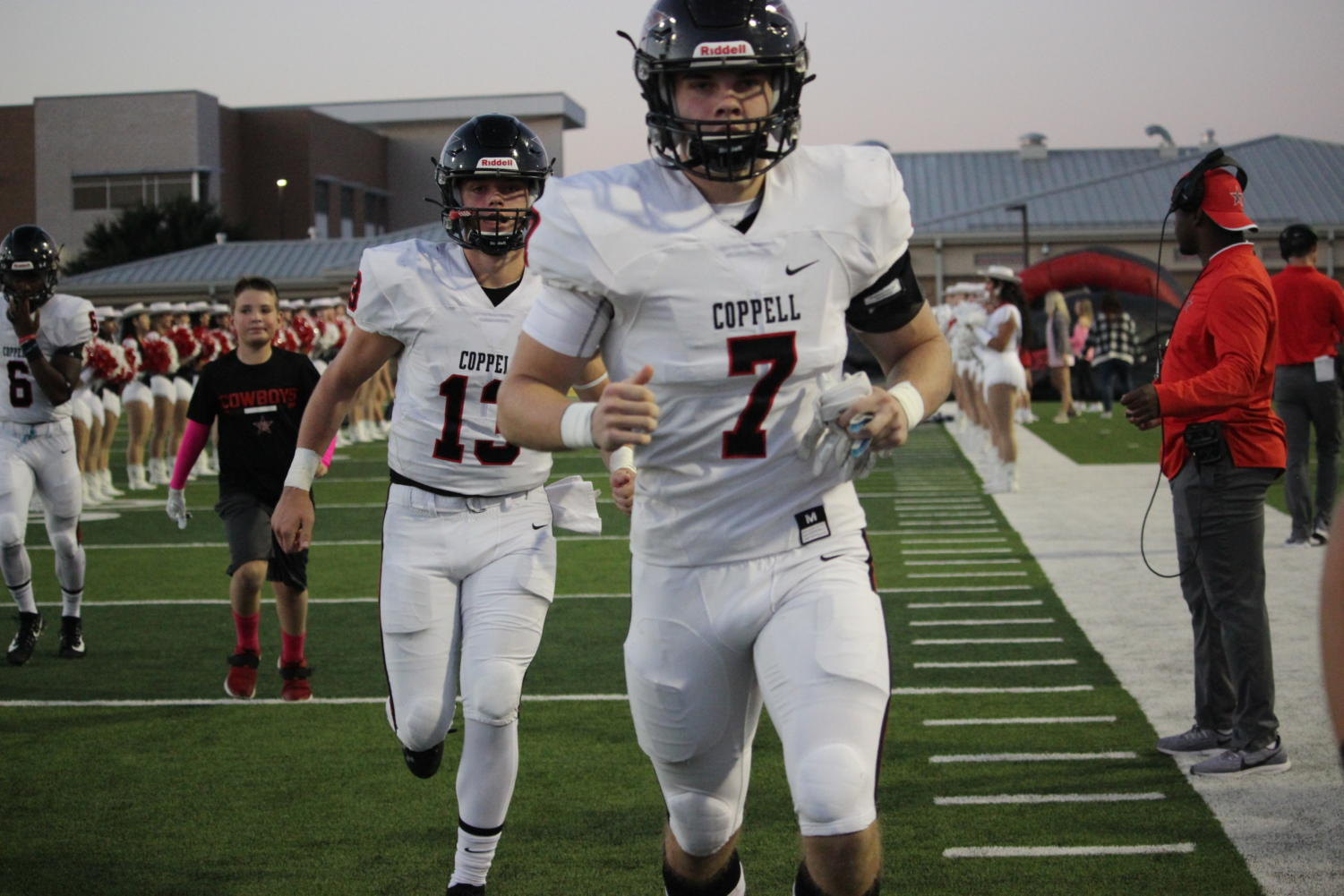 Coppell sophomore quarterback Landry Fee and senior defensive back Gavin Osteen run out during the game against Marcus on Oct. 18 at Marauders Stadium. The Cowboys face Irving tonight at 7 p.m. at Buddy Echols Field for the Homecoming game.