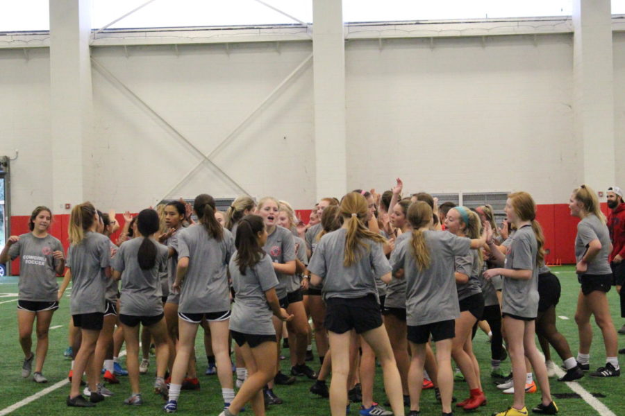 The Coppell girls soccer team high-fives each other after a warm up on Oct. 9 in the Coppell High School Field House. Cowgirls Supporting Cowgirls (CSC) is a group that promotes Coppell women's sports in order to increase attendance at their games.