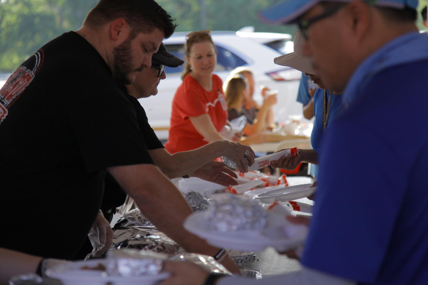 CHS9 Principal Cody Koontz serves food to parents, teachers and children. Coppell ISD hosted its home game tailgate in the Buddy Echols Field parking lot on Friday before the football game against Hebron.
