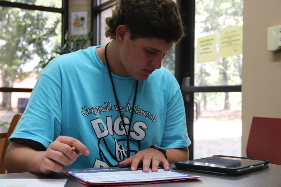 Coppell High School sophomore student council President Samuel Taylor marks important StuCo events in his calendar after school on Sept. 25 in the CHS Library. Taylor is excited to use his leadership position in StuCo to achieve his goals for the program.