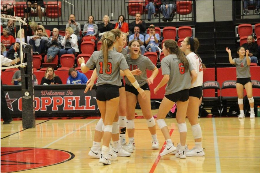 The Coppell volleyball team celebrate its victory in the CHS Arena on Friday. Coppell defeated Lewisville, 3-0.