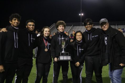The Coppell High School drumline team takes a picture with the Cardwell Cup on Nov. 9 at Marcus Marauder Stadium. The team receives first rank with a 96.88 rating in the Standstill I Silver Prelim part, Best Snare Line, Best Front Ensemble, Most Creative Drumline Show and The Cardwell Cup for Best Percussion Performance at Lone Star Classic 2019.