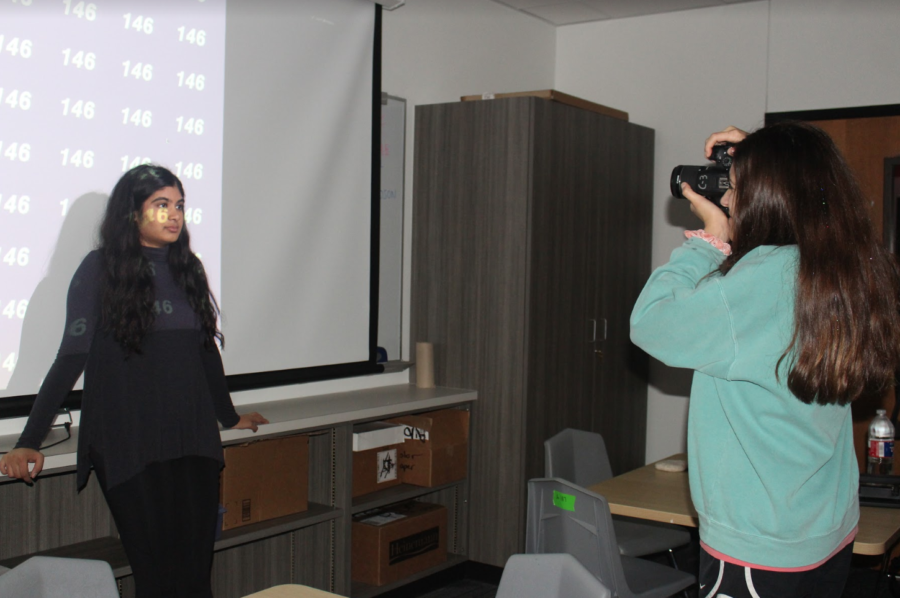 Coppell High School senior Anna Guzniczak takes a photo of senior Maya Mohan in Round-Up yearbook during seventh period today. The Round-Up classroom has shelf additions along with newly painted walls and redone flooring as part of the renovations in A Hall.