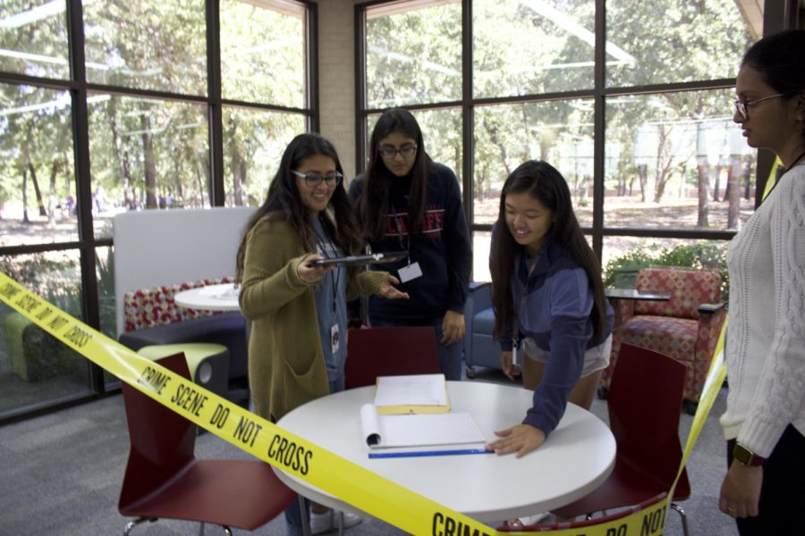 Coppell High School forensics students investigate a plotted crime scene in forensic teacher Sandy Kirkpatrick's third period class in the library on Oct. 7. Students take pictures and make educated guesses to solve the murder mystery.