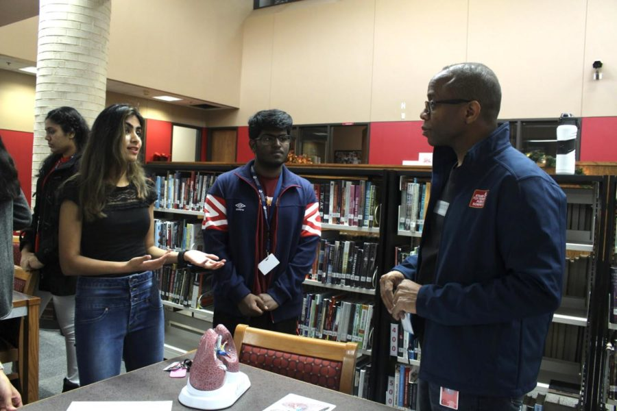 Coppell High School seniors Ady Chaudhari and Monish Ravishankar present their lung cancer awareness project to Coppell ISD Board of Trustee member Anthony Hill today in the CHS Library today during second period. Holly Anderson's International Baccalaureate (IB) biology class is holding a lung cancer awareness exposition in the library.