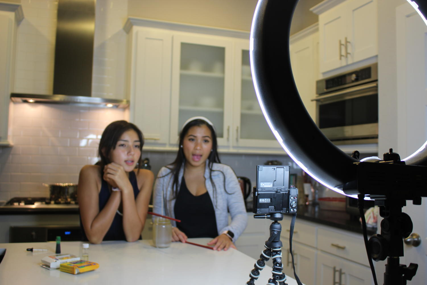 With help from her cousin, Ranchview High School sophomore Emma Immanivong (left), Coppell High School senior Alyson Immanivong films a DIY fall candle video on Oct. 7 for her YouTube channel. Immanivong posts videos every Wednesday on her channel that has more than 500 subscribers.