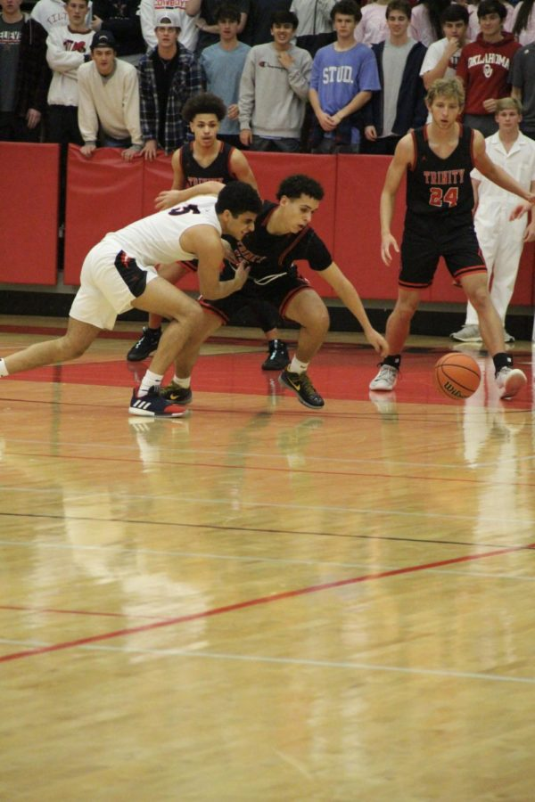 Coppel+senior+guard+Adam+Moussa+forces+a+loose+ball+in+the+CHS+Arena+on+Tuesday+against+Trinity.+Coppell+defeated+the+Trojans%2C+58-38.+