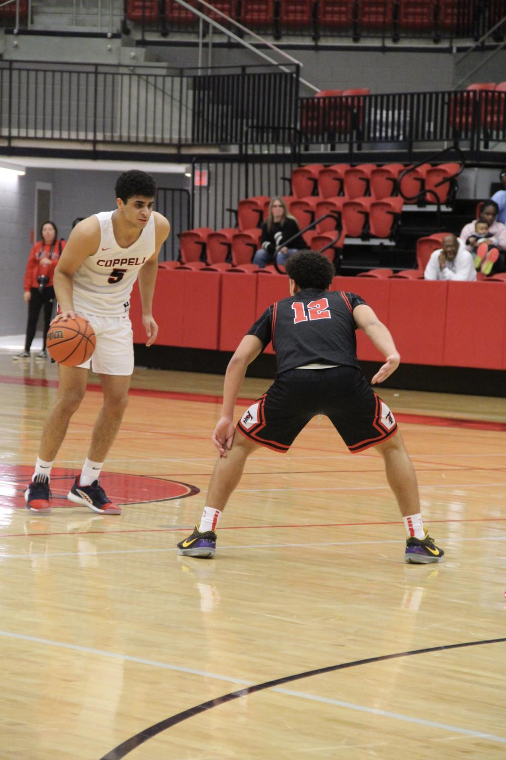 Coppel senior guard Adam Moussa looks to cross opponent in the CHS Arena on Tuesday against Trinity. Coppell defeated the Trojans, 58-38.