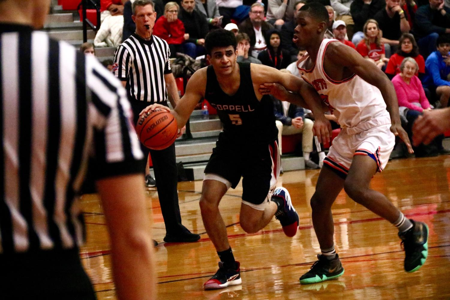 Coppell senior guard Adam Moussa dribbles around a Rockwall defender on Nov. 22 during the Classic Chevrolet Showcase in the CHS Main Gym. Moussa comes from a family of basketball players and is pursuing a future with the Egyptian national team, carrying the legacy of his father and older siblings.