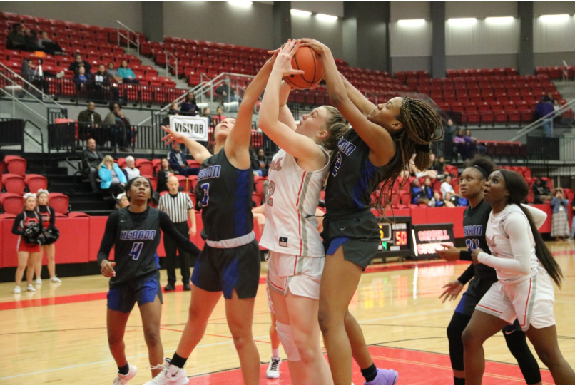 Coppell+freshman+Reagan+Engler+attempts+to+block+the+ball+from+two+Hebron+players.+The+Cowgirls+lost+to+the+Hebron+Hawks+53-44.