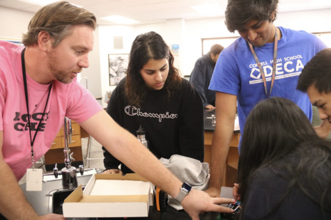 Coppell High School physics teacher and assistant baseball coach Clint Rushing assists CHS seniors Sophia Raza, Devan Patel, Andrew Tao and Vanuli Arya construct a working circuit board during his third period on Dec. 4. Rushing has taught at CHS for 11 years and was named The Sidekick's December teacher of the issue.