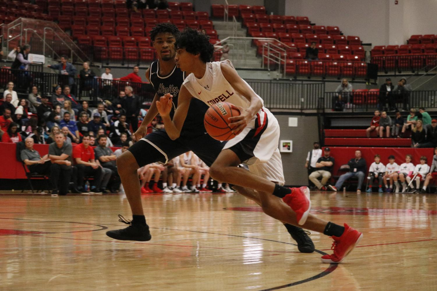 Coppell sophomore guard Ryan Agarwal shields the ball and attempts to make a play during the Cowboy's game against Irving Nimitz on Friday in the CHS Arena. The Vikings fell short to the Cowboys, 61-35, in their District 6-6A game. Photo by Sydney Rowe.