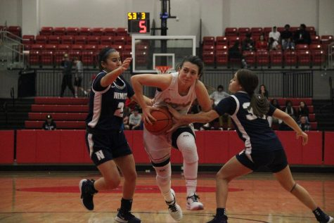 Coppell senior guard Megan O'Neil drives against Irving Nimitz guards Jocelyn De la Garza and Britney Gonzalez yesterday at the CHS Arena. The Cowgirls defeated Nimitz, 79-38.
