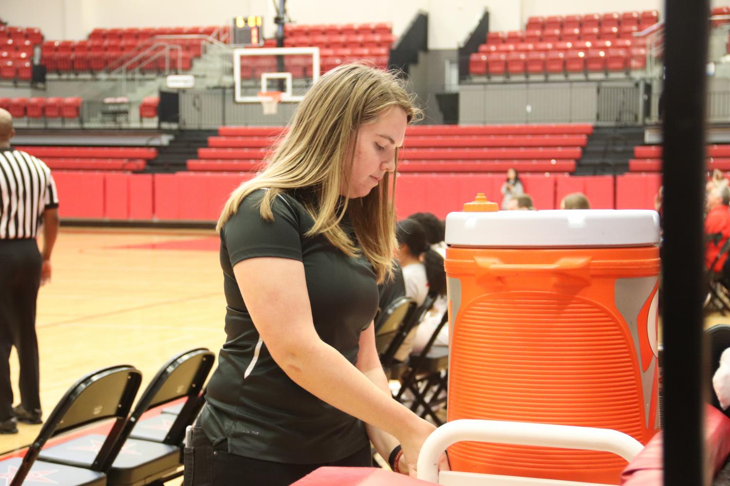 CHS/Coppell junior sports medicine trainer Taylor Evans fills water bottles for players at the varsity girls basketball game against Grapevine on Dec. 10 at the CHS Arena. Evans works exclusively with basketball during the winter season.