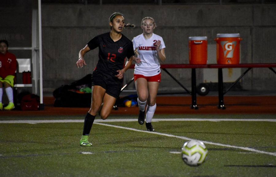 Coppell junior left forward Jojo Alonzo looks to pass against Irving MacArthur on Jan. 28 at Buddy Echols Field. Alonzo's unique ambidextrous abilities and versatility gained the attention on collegiate programs, allowing her to commit to the University of Memphis.