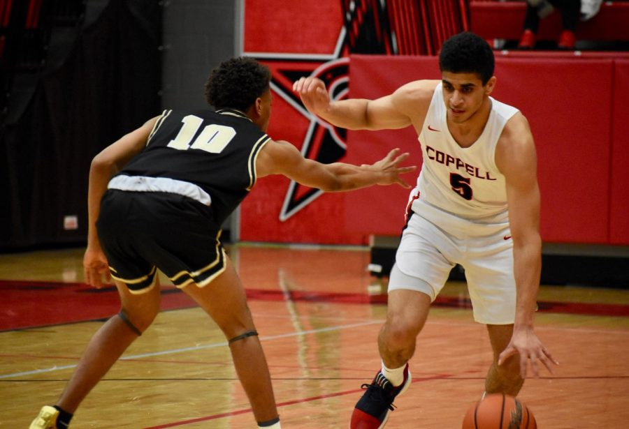 Coppell senior guard Adam Moussa dribbles past senior guard Dashawn Ford during the game against Irving on Saturday in the CHS Arena. The Cowboys won, 61-54, and play at Flower Mound on Tuesday at 8 p.m.